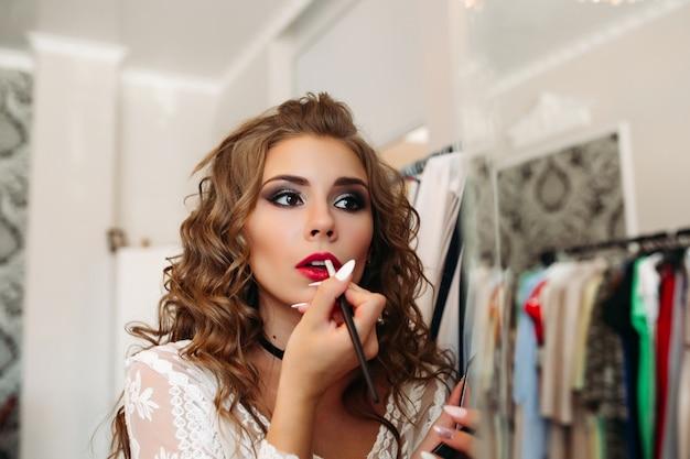 Porträt des mädchens lippenstift auf ihre lippen setzend und in spiegel schauend.
