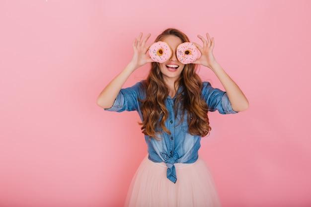 Porträt des mädchens mit dem langen haar, das rosa donuts als brille und lachen lokalisiert auf rosafarbenem hintergrund hält. entzückende lächelnde junge brünette junge frau, die spaß mit donuts nach dem teetrinken hat