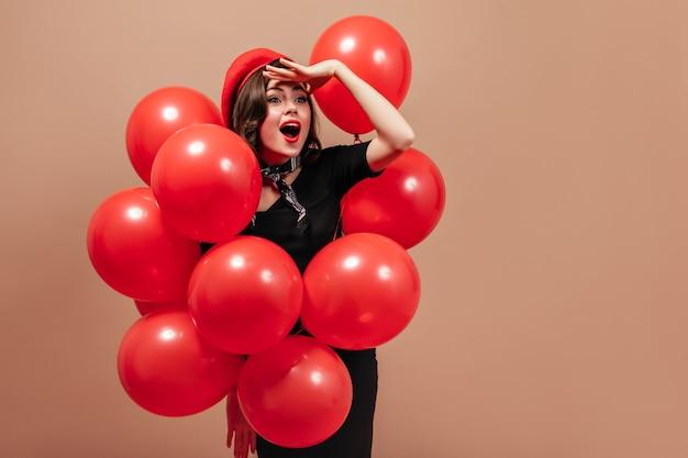 Porträt des mädchens mit den roten lippen, die mit luftballons aufwerfen. frau in baskenmütze schaut in die ferne.