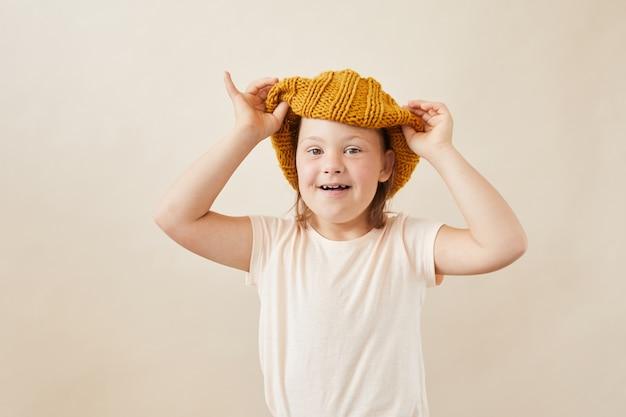 Porträt des mädchens mit down-syndrom, das wollhut trägt, der an der kamera gegen den weißen hintergrund lächelt