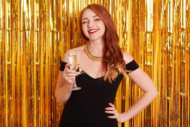 Porträt des mädchens mit glas champagner, posierend gegen wand verziert mit goldenem lametta, attraktive dame, die schwarzes kleid trägt, rothaarige lächelnde frau, die feiertag feiert.