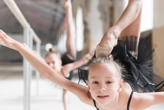 Porträt des mädchens mit ihrem bein, das oben während einer ballettklasse übt