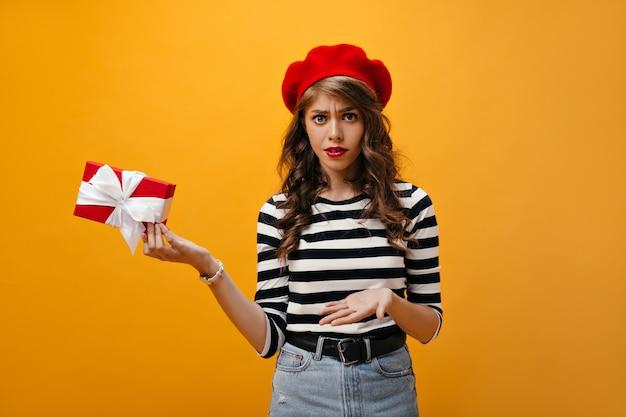 Porträt des mädchens sieht unglücklich aus und hält geschenkbox. moderne junge frau im roten baskenmützen- und jeansrock mit dem schwarzen gürtel, der aufwirft.