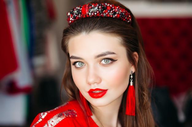 Porträt des mädchens tragend im roten, glänzenden haarband