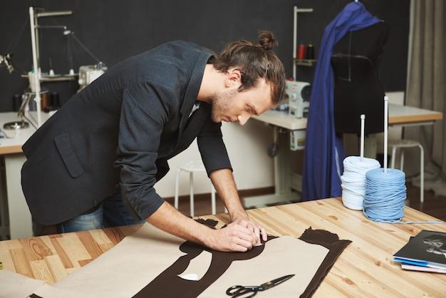 Porträt des männlich gut aussehenden erwachsenen männlichen kleidungsdesigners mit stilvoller frisur im schwarzen anzug, der teile des zukünftigen kleides aus stoff herausschneidet. der mensch konzentrierte sich auf die arbeit.