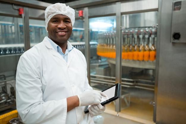 Porträt des männlichen arbeiters, der digitales tablett in der fabrik hält