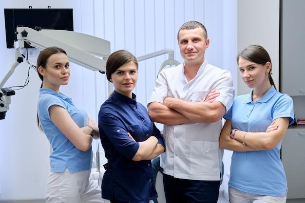 Porträt des männlichen arztzahnarztes und der weiblichen praktikanten in der zahnarztpraxis. personal, medizin, zahnmedizin und gesundheitswesen