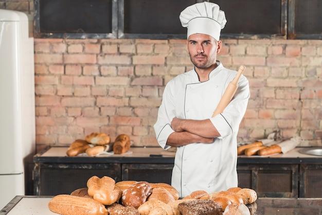 Porträt des männlichen bäckers das nudelholz halten, das hinter den gebackenen broten auf tabelle steht