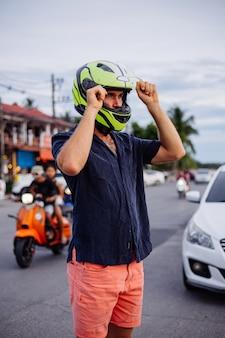 Porträt des männlichen bikers im gelben helm auf der seite der belebten straße in thailand zur sonnenuntergangszeit