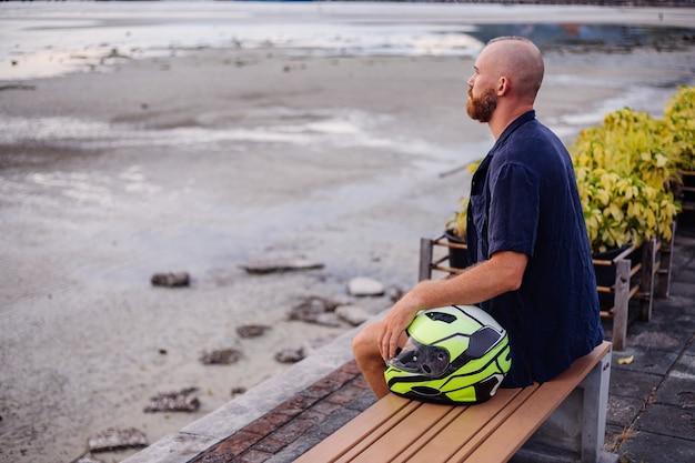 Porträt des männlichen bikers mit gelbem helm, der auf einer bank auf der promenade in thailand zur sonnenuntergangszeit sitzt