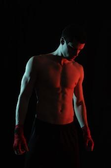 Porträt des männlichen boxers, der im roten und weißen licht aufwirft