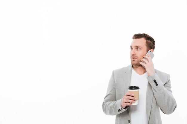 Porträt des männlichen büroangestellten kaffee zum mitnehmen beim haben des angenehmen beweglichen gespräches auf mobiltelefon und beiseite schauen, über weißer wand trinkend