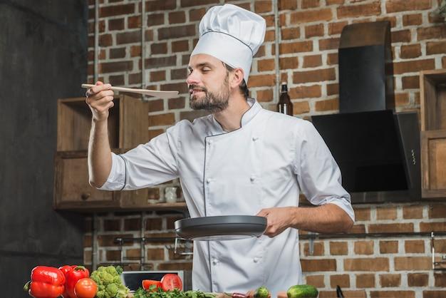 Porträt des männlichen chefs den geruch des zugebereiteten lebensmittels genießend