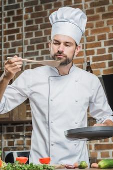 Porträt des männlichen chefs stehend in der küche, die lebensmittel schmeckt