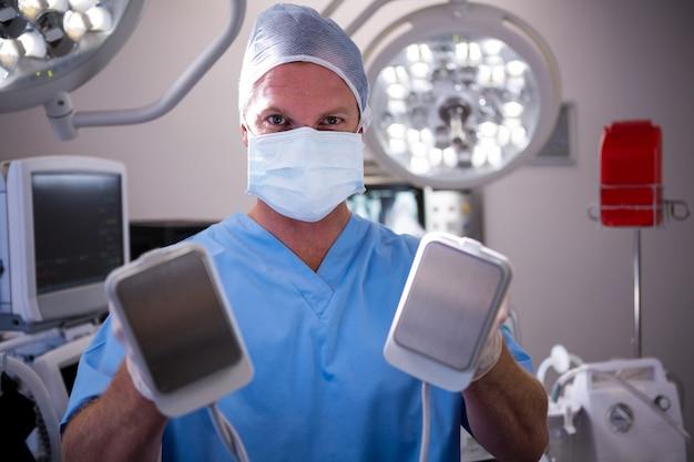 Porträt des männlichen chirurgen, der defibrillator hält
