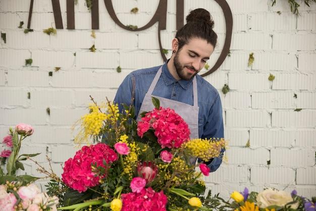 Porträt des männlichen floristen die mimose und die hortensie macrophylla blume vereinbarend, die blumenstrauß schafft