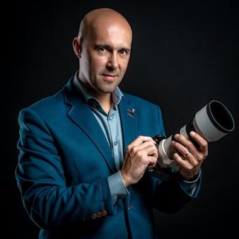 Porträt des männlichen fotografen mit kamera in den händen im studio auf schwarzem hintergrund