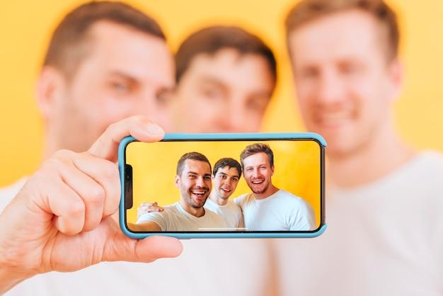 Porträt des männlichen freunds drei, der selfie auf smartphone nimmt