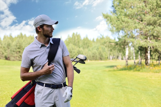 Porträt des männlichen golfspielers, der golftasche beim gehen durch grünes gras des golfclubs trägt.