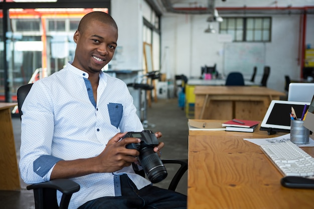 Porträt des männlichen grafikdesigners, der digitalkamera am schreibtisch hält