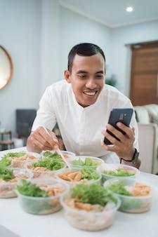 Porträt des männlichen hausverpflegungsdienstes, der lunchbox für online-bestellung zum mitnehmen vorbereitet