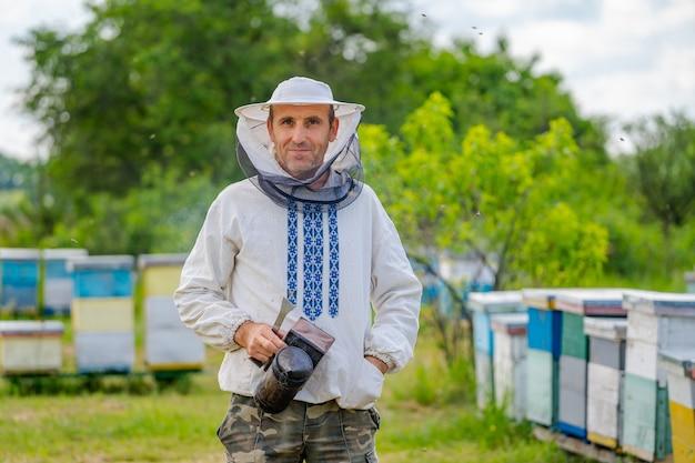 Porträt des männlichen imkers mit bienenstöcken im hintergrund. schutzkleidung an. bienenhaus.