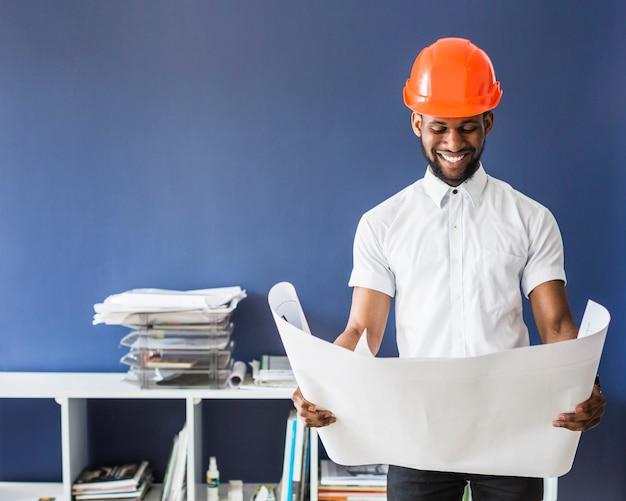 Porträt des männlichen ingenieurs einen orange hardhat tragend, der plan betrachtet