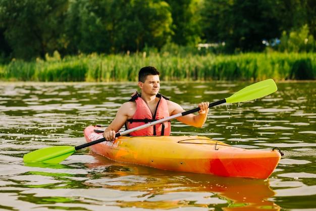 Porträt des männlichen kayaker kayak fahrend auf see