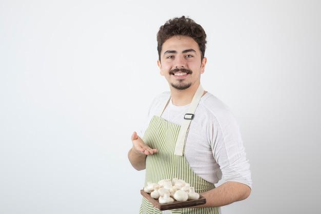 Porträt des männlichen kochs, der teller mit rohen pilzen auf weiß hält