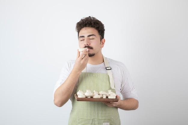Porträt des männlichen kochs riecht rohe pilze auf weiß