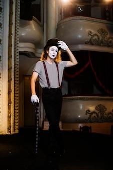 Porträt des männlichen künstlers des pantomimen, der mit regenschirm auf stadium aufwirft