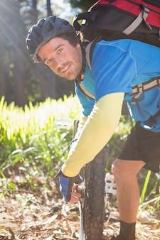 Porträt des männlichen mannes mountainbiker, der seine fahrradkette repariert