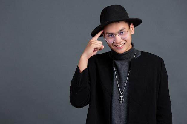 Porträt des männlichen modells, das finger zeigt und auf dunkler wand lächelt