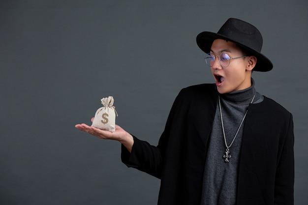 Porträt des männlichen modells, das sack der münze an der dunklen wand hält