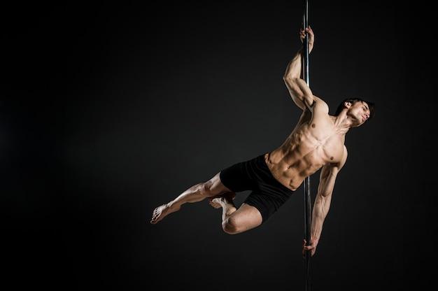 Porträt des männlichen modells einen stangentanz durchführend