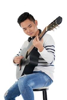 Porträt des männlichen musikers gesetzt auf dem schemel, der gitarre spielt