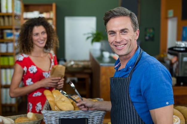 Porträt des männlichen personals, das am bäckereischalter steht