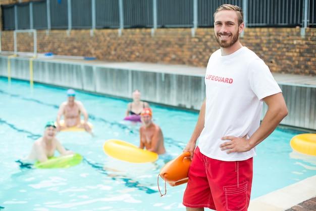 Porträt des männlichen rettungsschwimmers stehend, während schwimmer im pool schwimmen