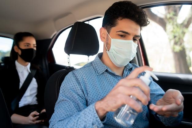 Porträt des männlichen taxifahrers, der gesichtsmaske trägt und alkoholgel auf setzt. neues normales lifestyle-konzept. transportkonzept.