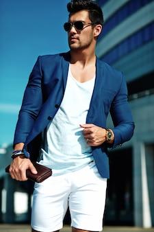Porträt des männlichen vorbildlichen mannes der sexy hübschen mode kleidete im eleganten anzug an, der auf der straße aufwirft. blauer himmel