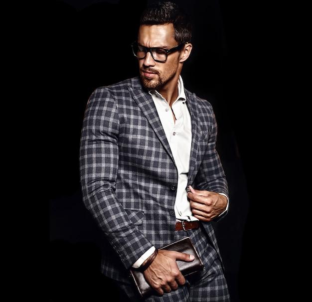 Porträt des männlichen vorbildlichen mannes der sexy hübschen mode kleidete im eleganten anzug auf schwarzem hintergrund an
