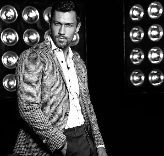 Porträt des männlichen vorbildlichen mannes der sexy hübschen mode kleidete im eleganten anzug auf schwarzem studio lichthintergrund an