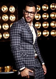 Porträt des männlichen vorbildlichen mannes der sexy hübschen mode kleidete im eleganten anzug auf schwarzem studio lichthintergrund in den gläsern an