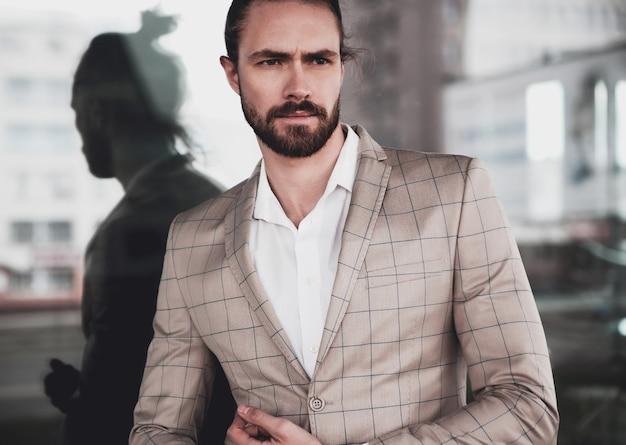 Porträt des männlichen vorbildlichen mannes der sexy hübschen mode kleidete im eleganten beige karierten anzug an, der auf dem straßenhintergrund aufwirft