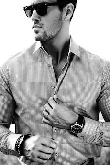 Porträt des männlichen vorbildlichen mannes der sexy hübschen mode kleidete im eleganten t-shirt an, das auf dem straßenhintergrund aufwirft. mit sonnenbrille
