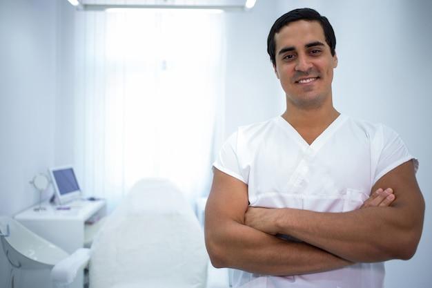 Porträt des männlichen zahnarztes, der mit verschränkten armen steht
