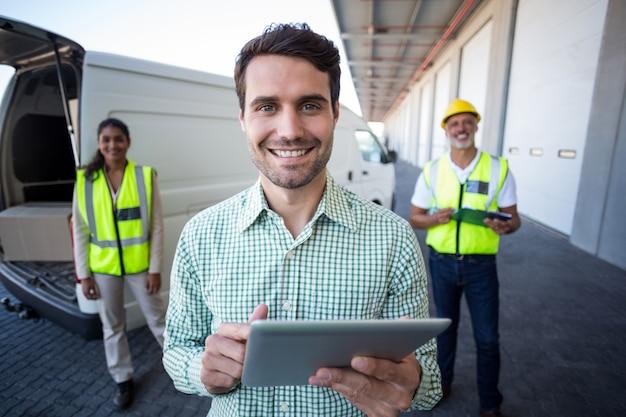 Porträt des managers mit digitalem tablet und arbeitern