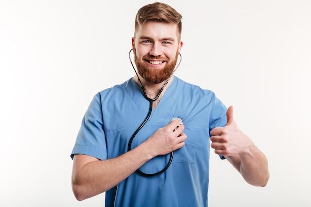 Porträt des mannarztes mit stethoskop, das daumen oben zeigt.