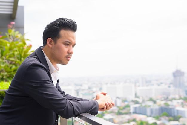 Porträt des mannes asiatischer geschäftsmann, der anzug trägt und auf dem dach denkt