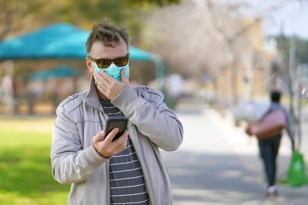 Porträt des mannes auf der straße in einer medizinischen maske und spricht am telefon. attraktives unglückliches modell mit grippe im freien. unglücklicher mann mit grippe im freien.